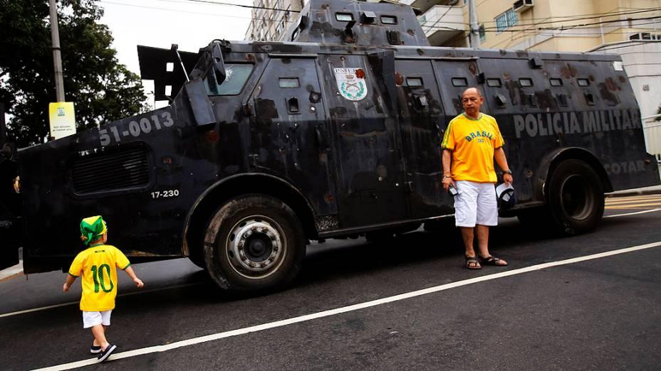 Torcedores brasileiros ao lado de um carro  Blindado da polícia fora do estádio do Maracanã antes da final da Copa das Confederações entre Brasil e Espanha, no Rio de Janeiro