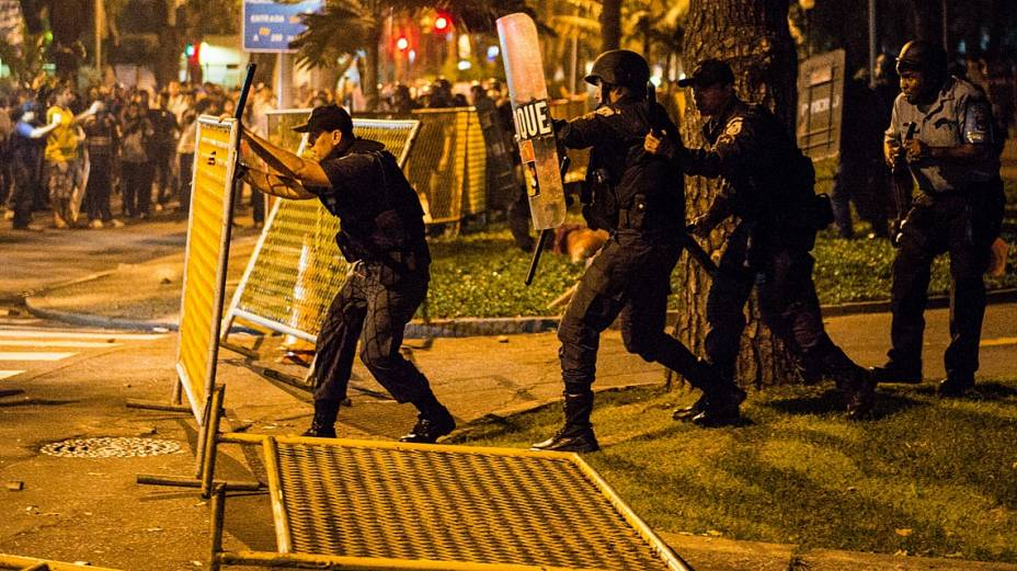 Policial recoloca gradil derrubado por manifestantes que isola área do Palácio Guanabara