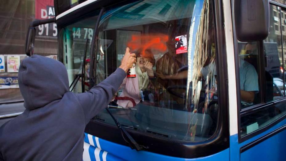 Manifestante picha ônibus durante greve geral em Madri para protestar contra medidas de austeridade do governo