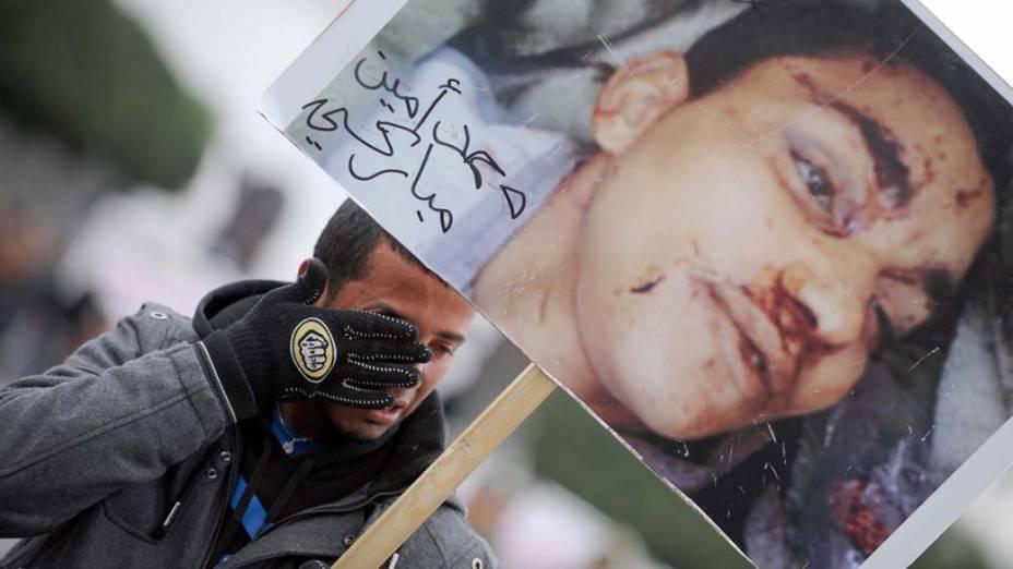 Tunisiano carrega foto de seu irmão morto durante protesto em frente ao palácio do governo na cidade de Túnis