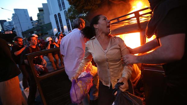 Mulher deixa o seu carro depois de manifestantes terem ateado fogo no veículo durante protesto contra a realização da Copa do Mundo