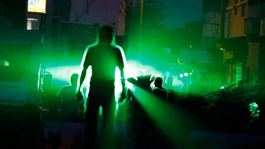 Manifestantes contrários ao governo gritam slogans frente a um emissor de laser em Manama, Barein