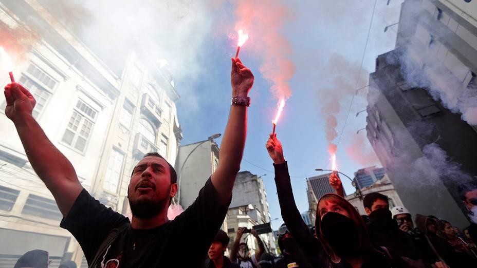 Rio de Janeiro - Manifestantes acendem sinalizadores e cobrem o rosto durante um protesto no centro do Rio