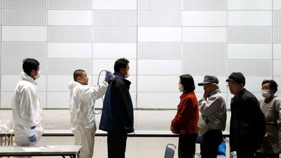 Oficiais medem nível de radiação em pessoas a 60km da usina nuclear de Fukushima, Japão