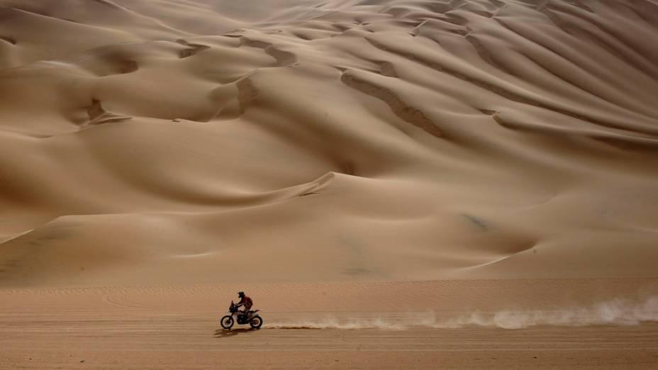 Motociclista atravessa deserto, durante a décima primeira etapa do rali Dakar, no Peru - 12/01/2012