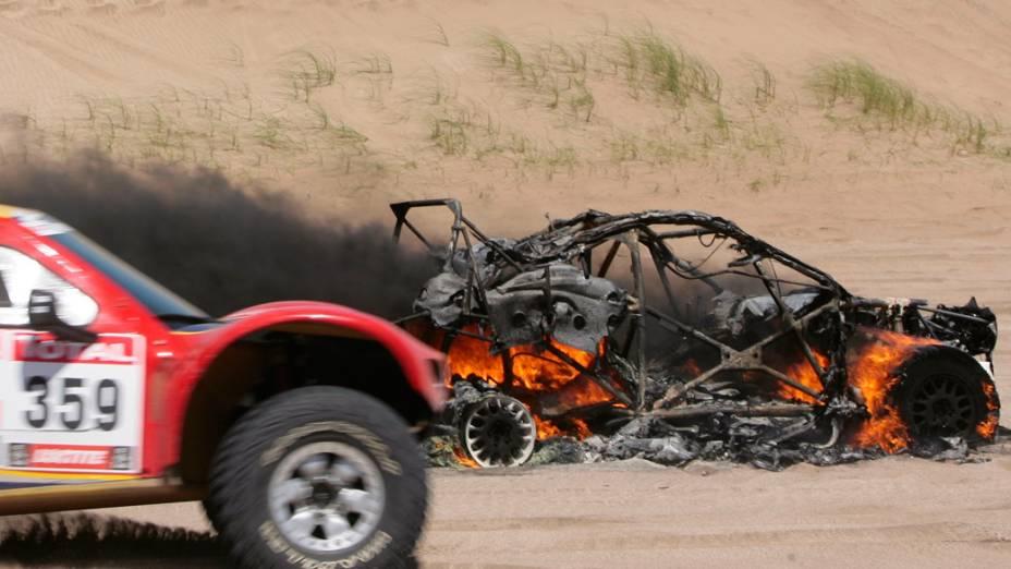 Competidor passa por veículo em chamas, da dupla Alfie Cox e Jurgen Schroeder, durante a primeira etapa do rali Dakar, na Argentina - 01/01/2012