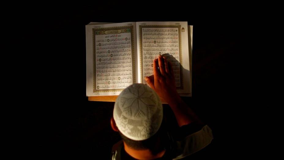 Muçulmano lê o Alcorão em uma mesquita da Palestina durante a oração matinal do Ramadã