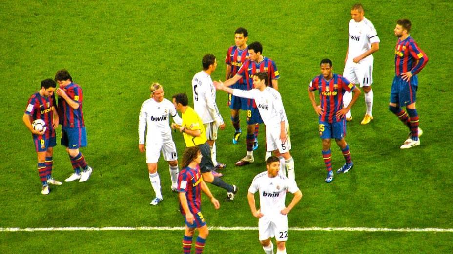 Em momento tenso do clássico, troca de empurrões entre jogadores; enquanto isso, Messi e Xavi combinam seu posicionamento em campo