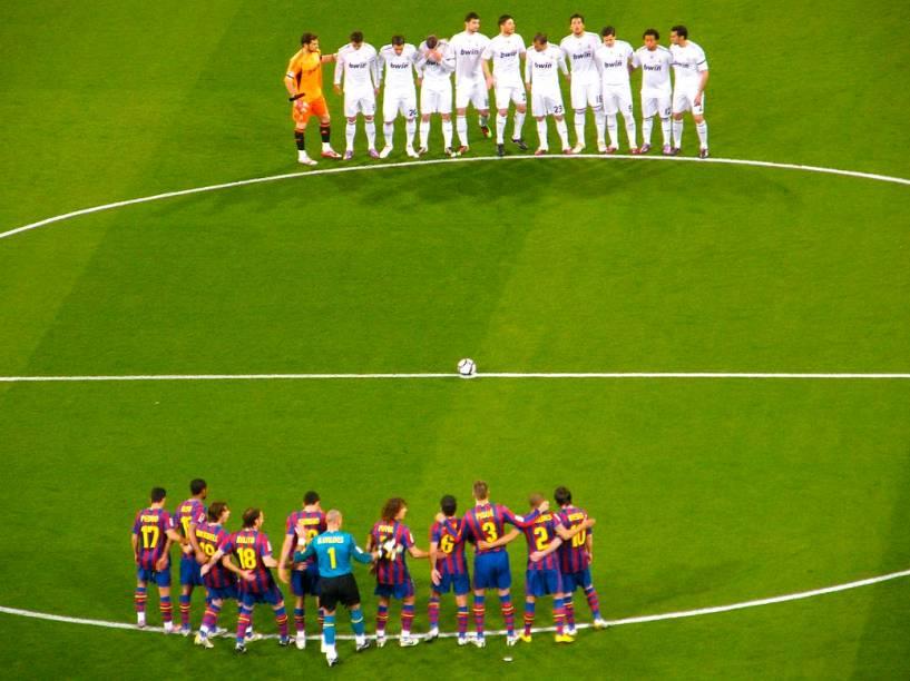 Os times do Real Madrid e do Barcelona se reúnem no centro do gramado para respeitar um minuto de silêncio antes do início da partida