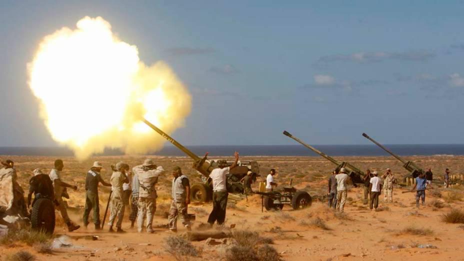 Rebeldes líbios lançam fogo em Om El Khanfousa, a leste de Sirte, Líbia