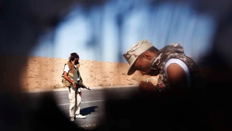 Rebeldes em estrada da cidade de Bani Walid, na Líbia