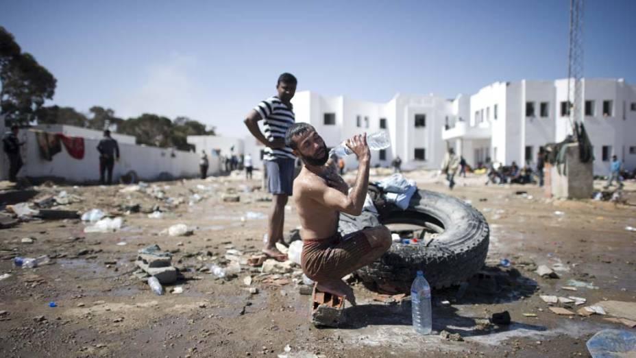 Refugiado se refresca em abrigo provisório na cidade de Ras Jedir, na fronteira entre a Tunísia e a Líbia