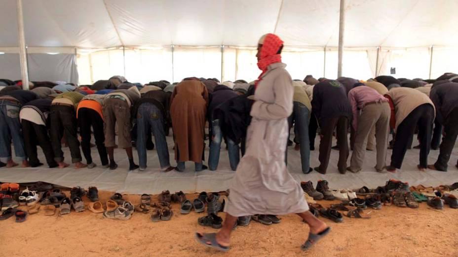 Imigrantes fugidos da Líbia rezam em mesquita improvisada na fronteira com a Tunísia, na cidade de Ras Jedir<br>