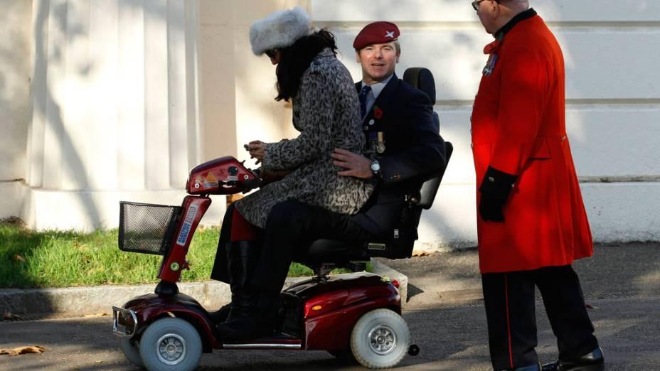 """Veterano ferido em guerra leva a esposa em cadeira motorizada, durante a cerimônia do """"Remembrance Day"""", em Londres"""