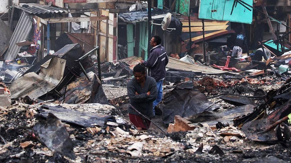 Moradora caminha na favela do Piolho, no Campo Belo, zona sul de São Paulo, no dia seguinte ao incêndio que atingiu o local, nesta segunda