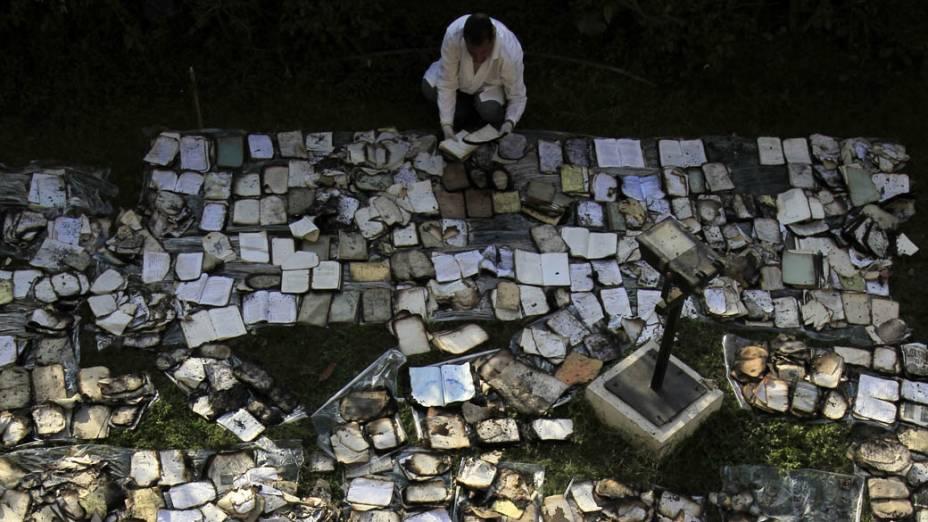 Restaurador seca livros danificados em incêndio, causado durante confrontos, no Instituto do Egito, fundado em 1798, que contém mais de 20.000 documentos e manuscritos, no Cairo