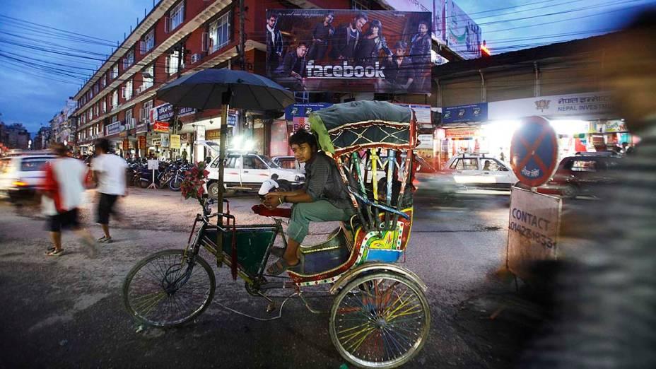Menino aguarda por passageiros em rickshaw, no Nepal