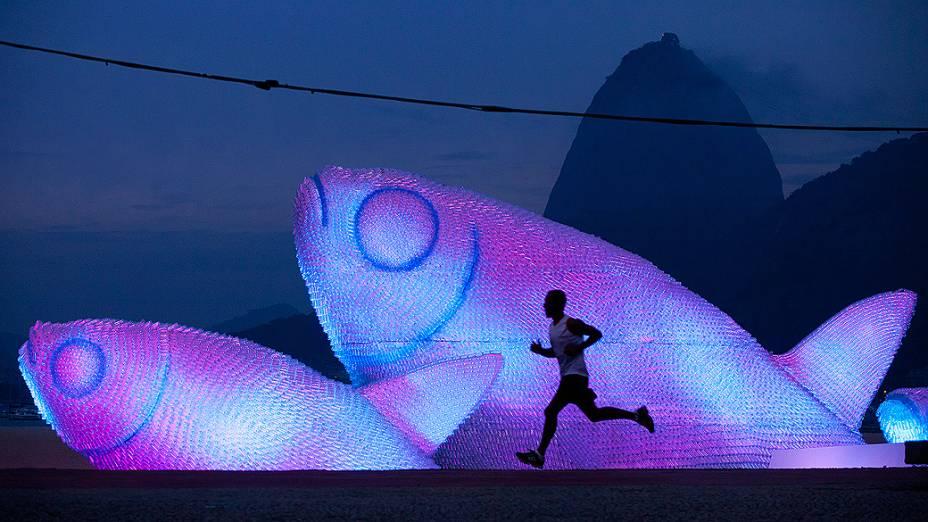 Homem corre próximo a escultura feita de garrafas plásticas na praia de Botafogo, Rio de Janeiro