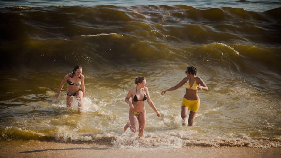 As pessoas tentam aliviar o forte calor com poucoas roupas, bastante líquido e mergulhos na praia, no Rio de Janeiro