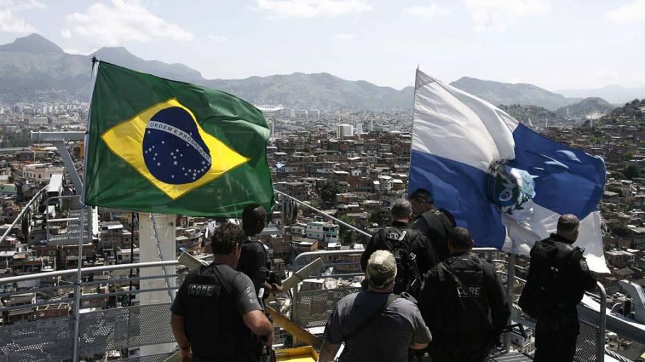 Policiais colocam as bandeiras do Brasil e do Estado do Rio de Janeiro após a ocupação do Complexo do Alemão em 28 de novembro