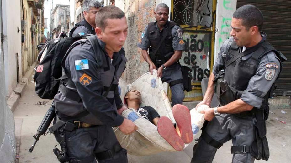Policiais carregam suspeito morto durante troca de tiros na comunidade Mandela 2, no Rio de Janeiro