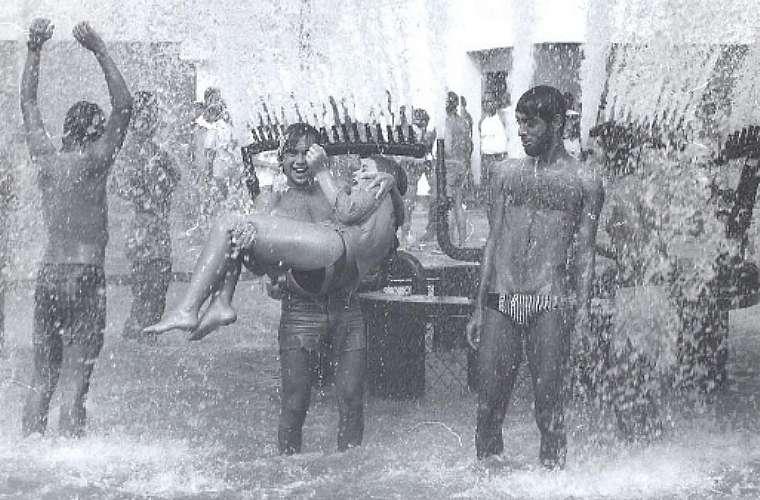 Jovens se banham no chafariz do Rock in Rio para aliviar o calor.