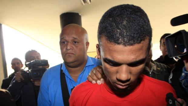 Sérgio Rosa Sales é conduzido por policiais da carceragem para a sala onde acontece a acareação, em Belo Horizonte.