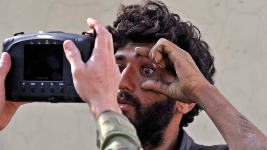 No Afeganistão, soldado americano escaneia os olhos de cidadão afegão com um aparelho de identificação biométrica, durante missão na cidade de Turkham