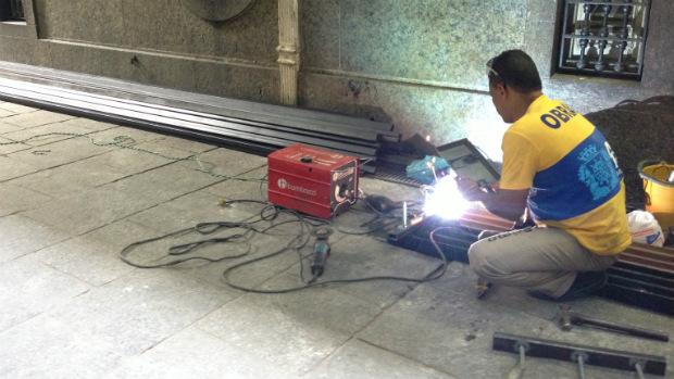 Funcionário prepara barras de ferro fixadas no portão lateral da Câmara de Vereadores do Rio