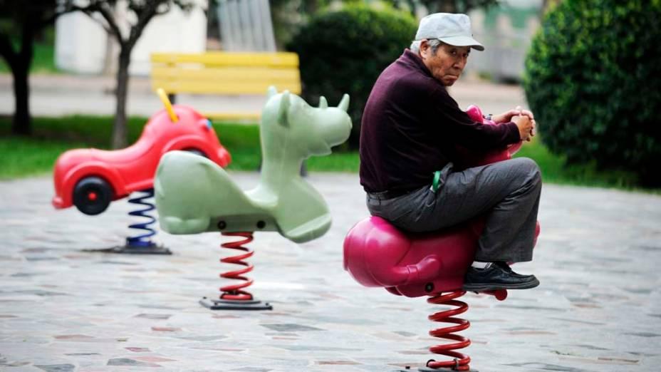 Senhor em um brinquedo infantil numa praça de Pequim, China