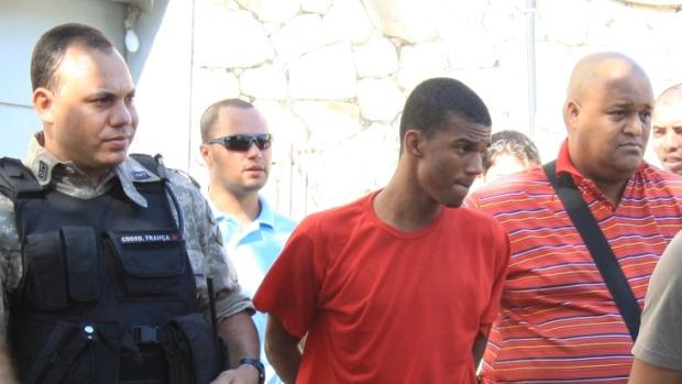 Sérgio Rosa Sales, de uniforme vermelho, é conduzido por policiais: primo do jogador Bruno mudou versão de depoimento e, agora, diz que o goleiro não foi ao local da execução de Eliza Samudio.<br>