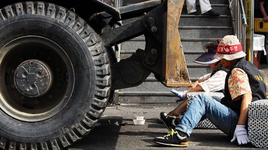 Ambulantes sul-coreanos protestam, sentados no chão, contra proibição do comércio informal nas ruas de Seul