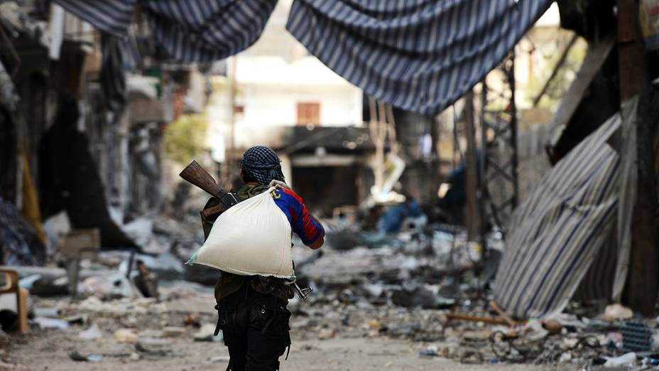 Rebelde carrega saco de areia, na Síria