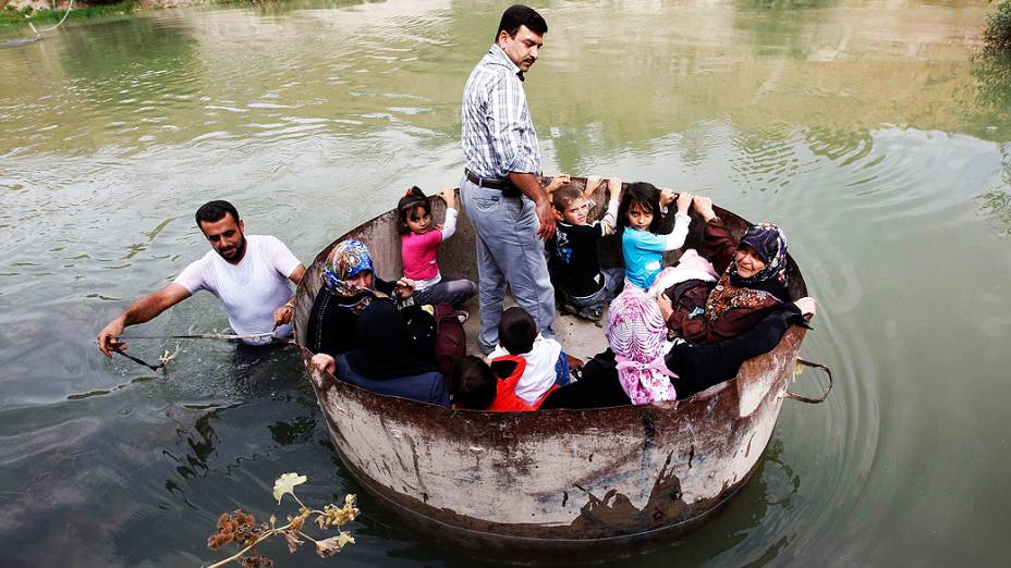 Sírios cruzam a fronteira com a Turquia pelo rio Orontes, perto da vila de Hacipasa. Dezenas de civis sírios, muitos deles mulheres e crianças, cruzaram o rio na tentativa de fugir dos combates