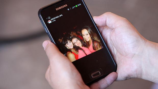 O pai de Jennefer, Adherbal Alves Ferreira, segura celular com foto da filha
