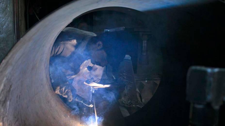 Funcionário soldafolha de metal em oficina de Faisalabad, Paquistão