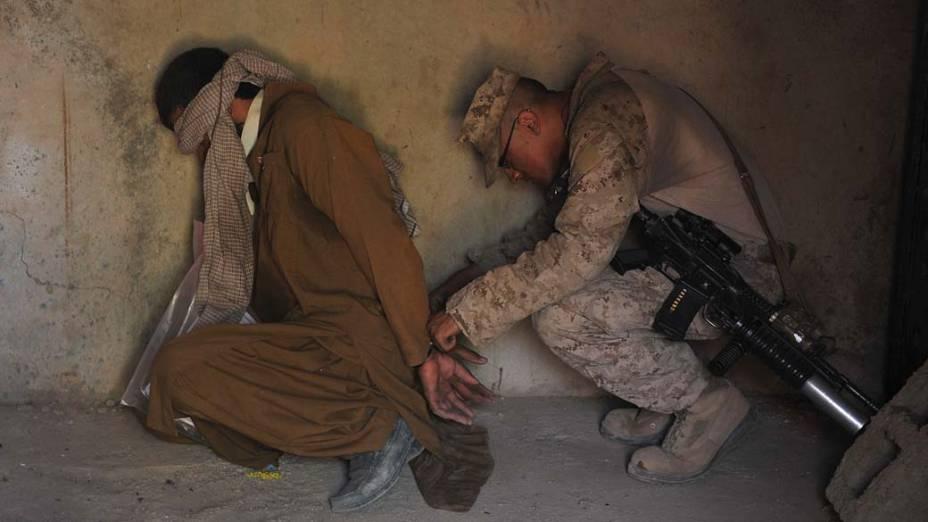 Soldado americano confere as algemas de um prisioneiro na cidade de Helmand, Afeganistão