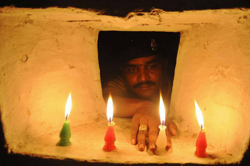 Soldado acende vela em comemoração ao festival Diwali, conhecido como festival das luzes, em Agartala, na Índia
