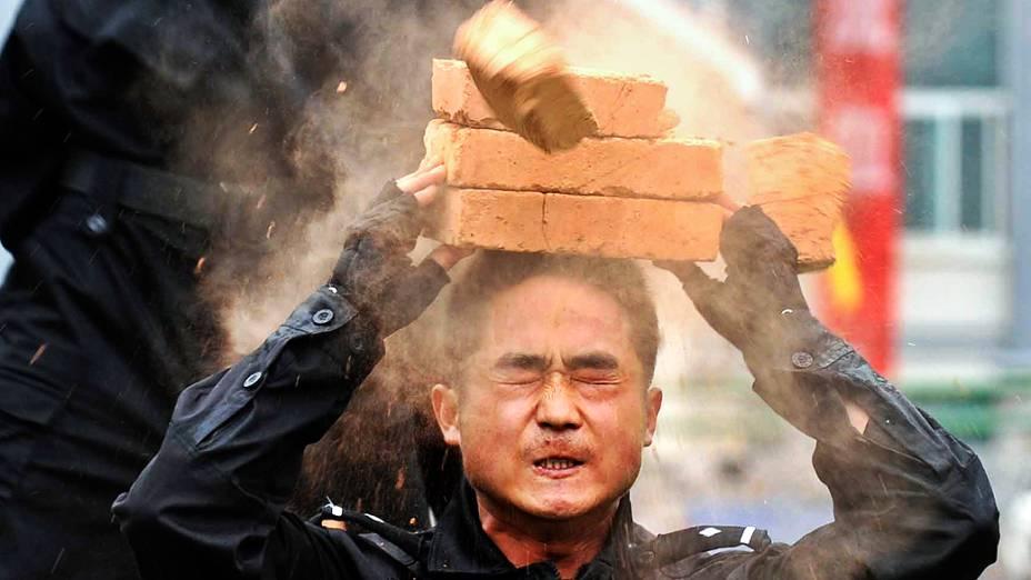 Policial quebra tijolo na cabeça em treinamento antiterrorismo no condado de Wengan, na China