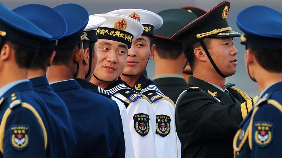 Membros da guarda de honra chinesa esperam pela chegada do presidente da Rússia, Vladimir Putin, ao Aeroporto Internacional de Pequim, na China