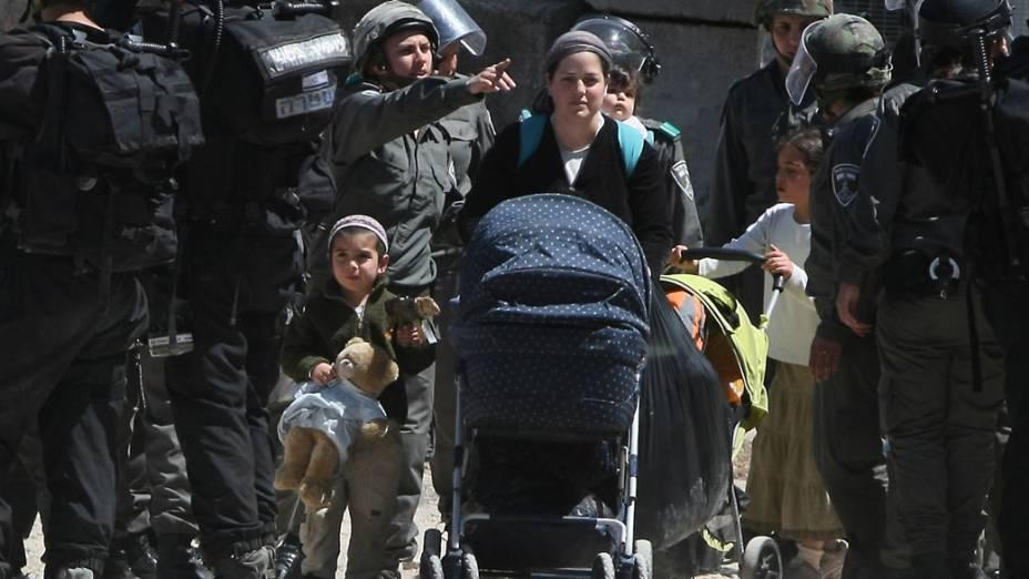 Em Hebron, soldados israelenses escoltam família que foi obrigada a deixar sua casa na região de conflito na Cisjôrdania