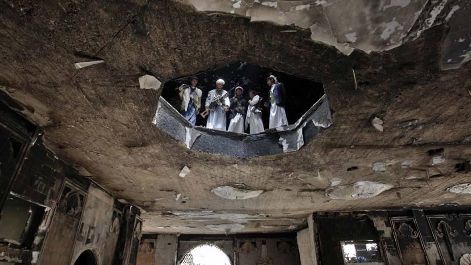 Soldados leais do líder tribal Sheik Sadiq al-Ahmar inspecionam casa destruída em Sanaa, Iêmen