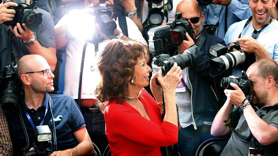 A atriz Sophia Loren (c) tira uma foto dos fotógrafos no Festival de Cannes, nesta quarta-feira (21)