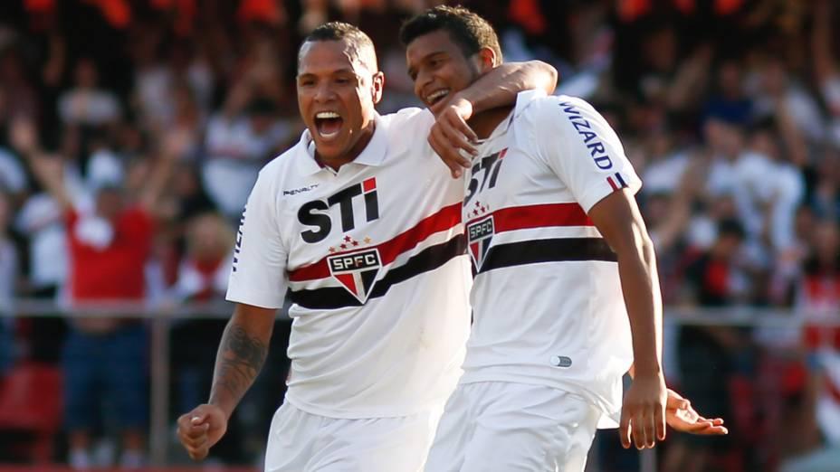 O jogador Luis Fabiano comemora o segundo gol do time do São Paulo, feito pelo jogador Reinaldo (d), durante partida contra o Fluminense
