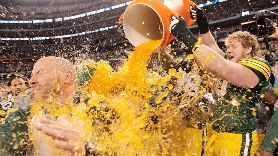 Jogadores do Green Bay Packers comemoram a vitória no Super Bowl XLV dando banho em seu treinador