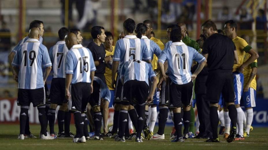 Jogadores de Brasil e Argentina aguardam o início do Superclássico das Américas, em Resistência, depois da falha no sistema de iluminação