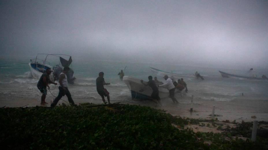 Pescadores tentam segurar seus barcos durante tempestade tropical na cidade de Mahahual, México