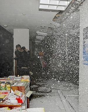 Trabalhadores se protegem de parte do teto que desabou após terremoto na cidade de Sendai.