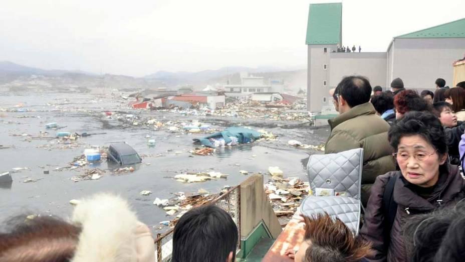 Pessoas observam a destruição do tsunami no porto de Kessennuma, Japão