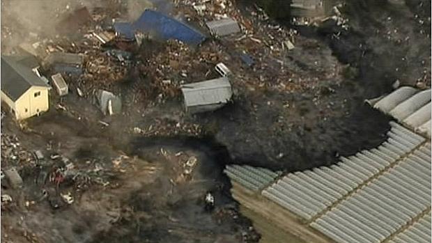 Casas são arrastadas pelas águas na cidade de Sendai, na tarde desta sexta-feira, após tsunami atingir a costa japonesa